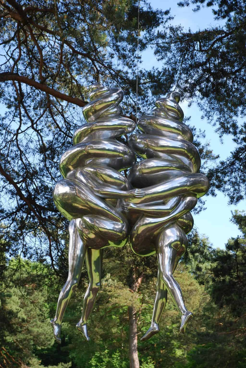 In einem Park in Oslo hängen zwei Metallfiguren in den Bäumen